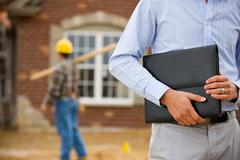 construction: agent holding portfolio with worker in background - stock photo