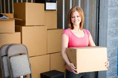 Storage: woman with boxes behind Stock Photos