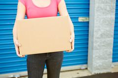 Storage: woman with box stands by door Stock Photos