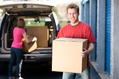 Storage: man holding box with woman behind Stock Photos