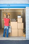 storage: man adds to storage unit - stock photo