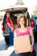 storage: woman carries box from truck - stock photo