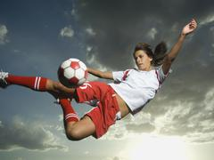 Low angle view of soccer player jumping Stock Photos