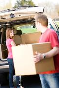 storage: man helping woman with boxes - stock photo