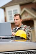 Construction: contractor using laptop for work Stock Photos
