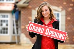 construction: woman holds up grand opening sign - stock photo