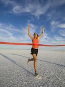 Woman running across finish line, Utah, United States Stock Photos