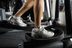 Stock Photo of Woman exercising on elliptical machine