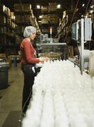 Hispanic female factory worker checking product Stock Photos