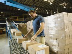 Varastotyöntekijä tarkkailun paketteja liukuhihnalta Kuvituskuvat
