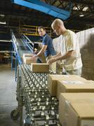 Warehouse workers checking packages on conveyor belt Stock Photos