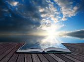 Stock Photo of creative concept pages of book stunning landscape at sunset reflected in ocea