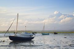 Summer evening landscape of leisure boats in harbor at low tide Stock Photos