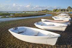 Small leisure boats moored at low tide in marina at summer sunset Stock Photos