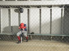 Sad baseball player sitting in dugout - stock photo