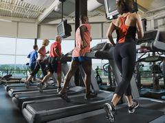 Men and women running on treadmills - stock photo