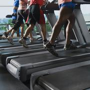 Men and woman running on treadmills - stock photo