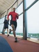 Men running on indoor track - stock photo