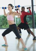 Fitness class doing shoulder presses with dumbbells Stock Photos