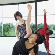Yoga instructor helping woman with triangle pose - stock photo