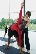 Yoga instructor helping man with triangle pose - stock photo