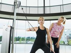 Personal trainer standing behind woman exercising Stock Photos