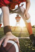 Football center preparing to snap football to quarterback - stock photo