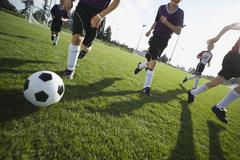 Boys playing competitive soccer - stock photo