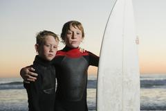 Children posed with surfboard - stock photo