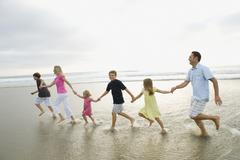 Family holding hands in ocean Stock Photos
