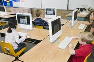 Children working at computers in classroom Stock Photos