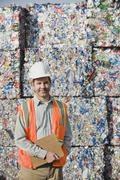 Worker standing in front of crushed aluminum cans - stock photo