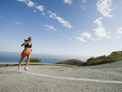 Woman running on a road in Malibu Stock Photos