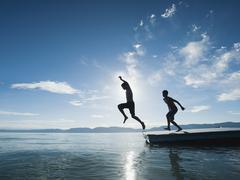 Boys (10-11,12-13) jumping from raft Stock Photos