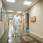 Senior man in hospital walking with walker - stock photo