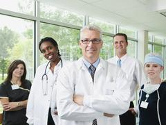 Male and female doctor, hospital manager and nurse posing for portrait - stock photo