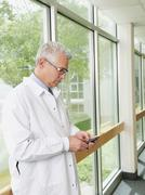 Doctor using mobile phone while standing in hospital corridor - stock photo