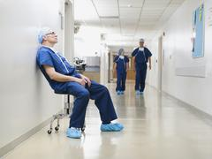 Surgeon resting in hospital corridor after operation, while two of his Stock Photos