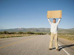 Stock Photo of Mid-adult man hitch-hiking in barren scenery