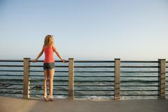 Stock Photo of Young attractive woman contemplating seascape from terrace