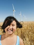 Stock Photo of USA, Oregon, Wasco, Cheerful girl (10-11) standing in wheat field with wind