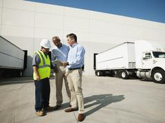 Business men and worker talking outside warehouse Stock Photos