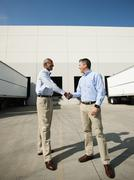 Business men shaking hands outside warehouse Stock Photos