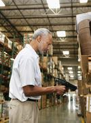 Warehouse worker scanning delivery - stock photo