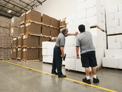 Warehouse workers inspecting delivery - stock photo