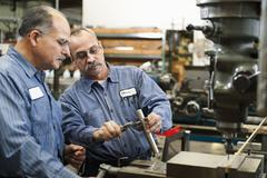 Skilled workers in factory Stock Photos