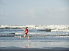 Young adult man running on beach Stock Photos
