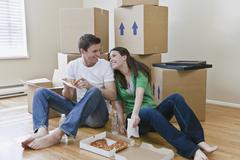 Couple eating pizza by packed boxes Stock Photos