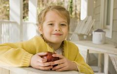 Stock Photo of Girl eating apple porch