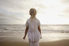 Girl looking out at ocean - stock photo